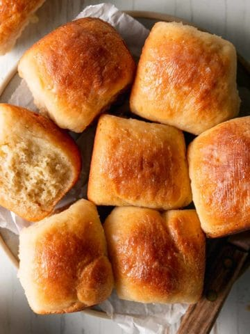A plate of gluten free Hawaiian rolls, one on it's side to show texture.