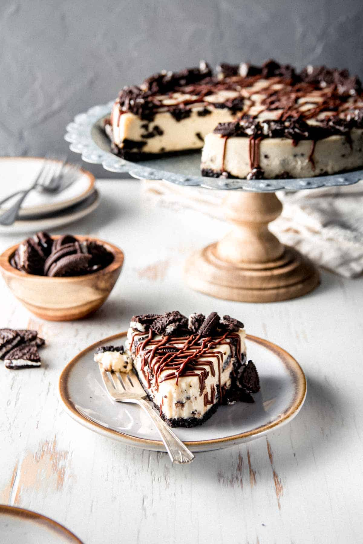 A slice of gluten free Oreo cheesecake on a plate drizzled with chocolate ganache. A bite is taken.