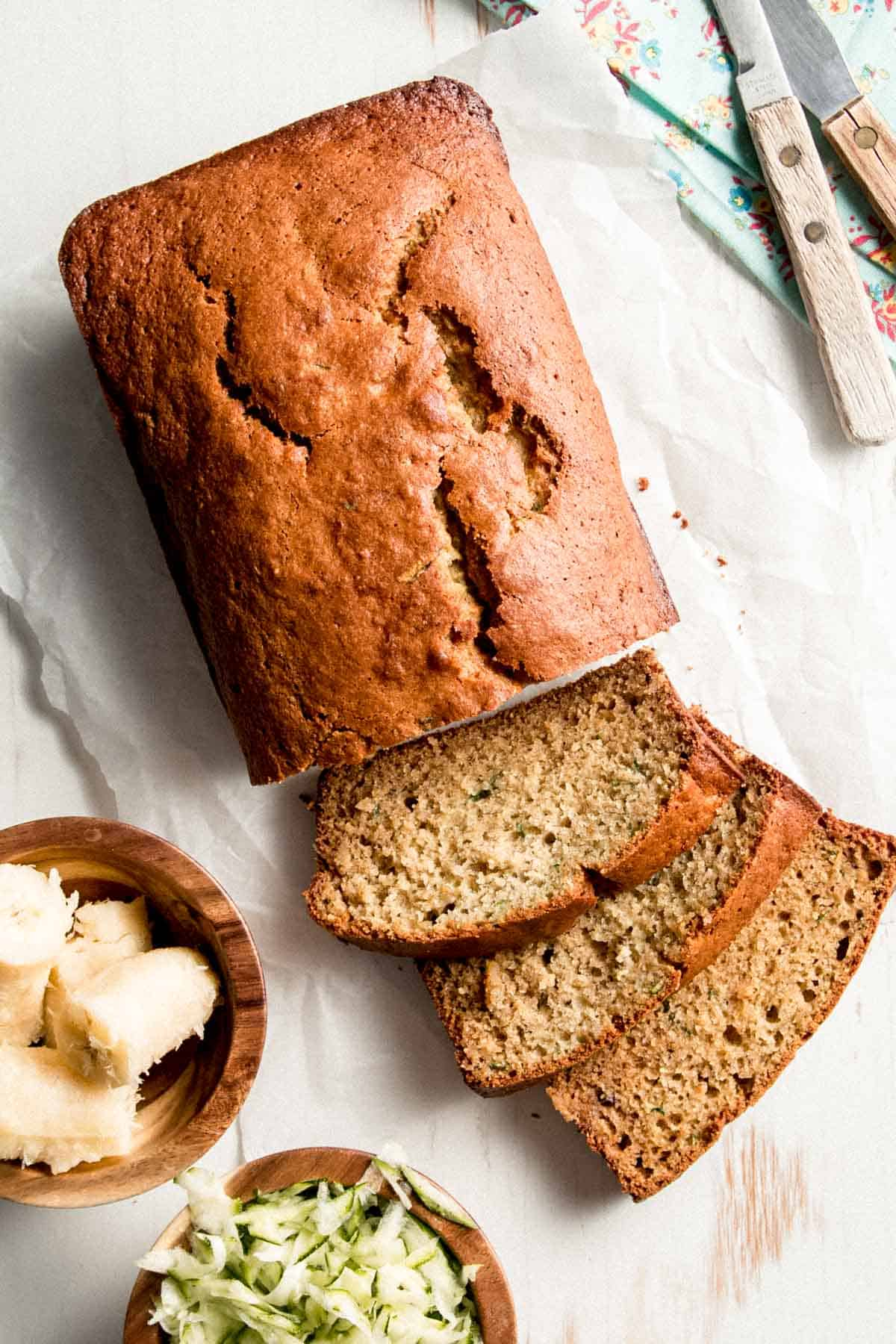 A loaf of Gluten-free Zucchini Banana Bread with a few slices laid on their sides next to small bowls of ripe banana and grated zucchini.