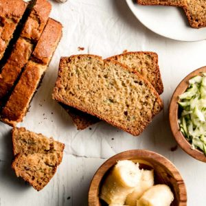 Gluten-free Zucchini Banana Bread sliced, laid on it's side, next to the rest of the loaf and a dish of zucchini and banana.