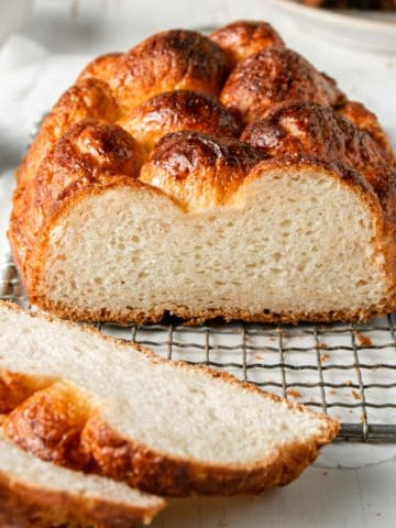 Braided gluten-free brioche loaf on wire rack, partially sliced to show interior texture.
